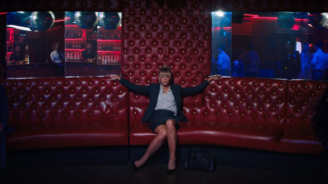 Cassie (Carey Mulligan) sits on a giant red couch in front of mirrors in Promising Young Woman