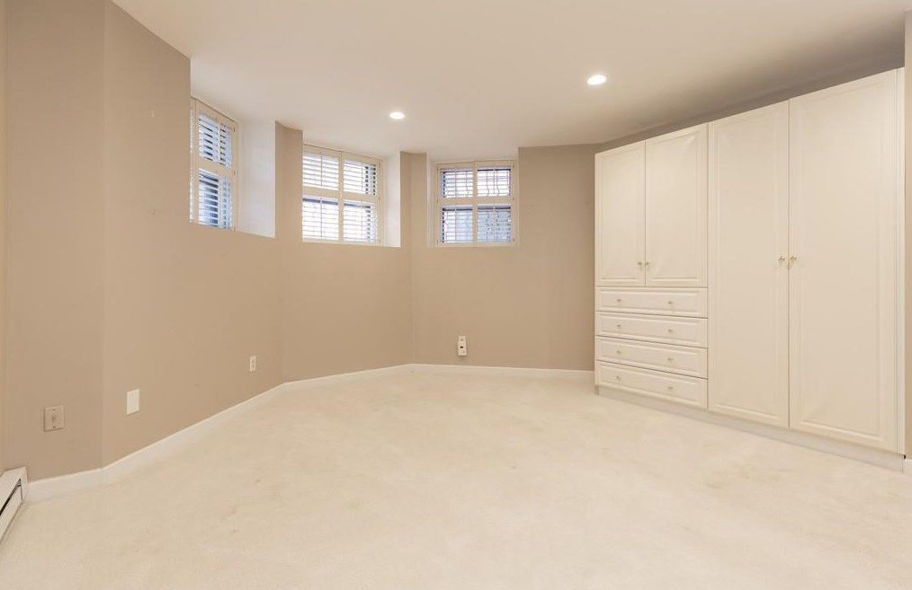 An empty bedroom with a large set of cabinets and windows toward the ceiling.