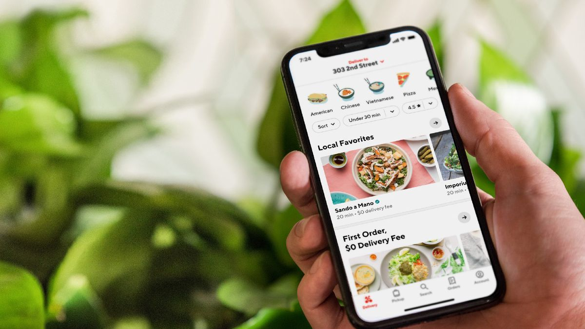Photo of man holding cellphone, looking at food delivery options