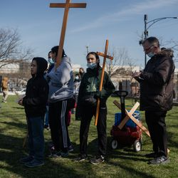 A family attends Via Crucis on the field of St. Procopius Catholic Church in Pilsen, Friday morning, April 2, 2021. The annual Via Crucis is a Good Friday tradition that reenacts the Stations of the Cross, a Catholic devotion that recounts Jesus' passion and death.