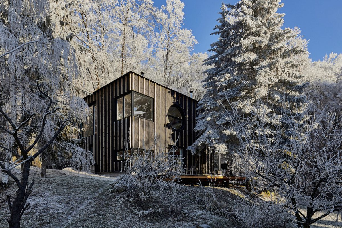 A simple rectilinear wood structure in the snowy woods.