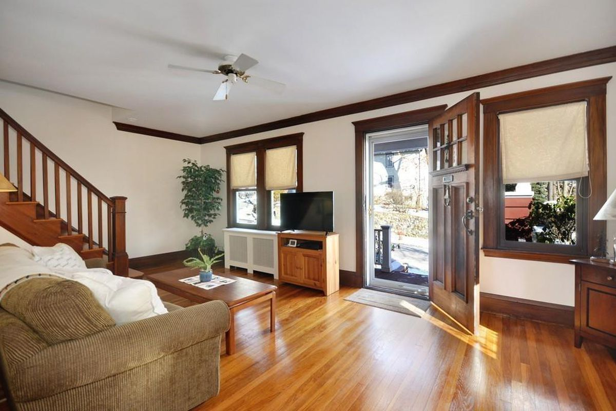 A large, sunny entry foyer with a radiator and a staircase leading from the foyer.