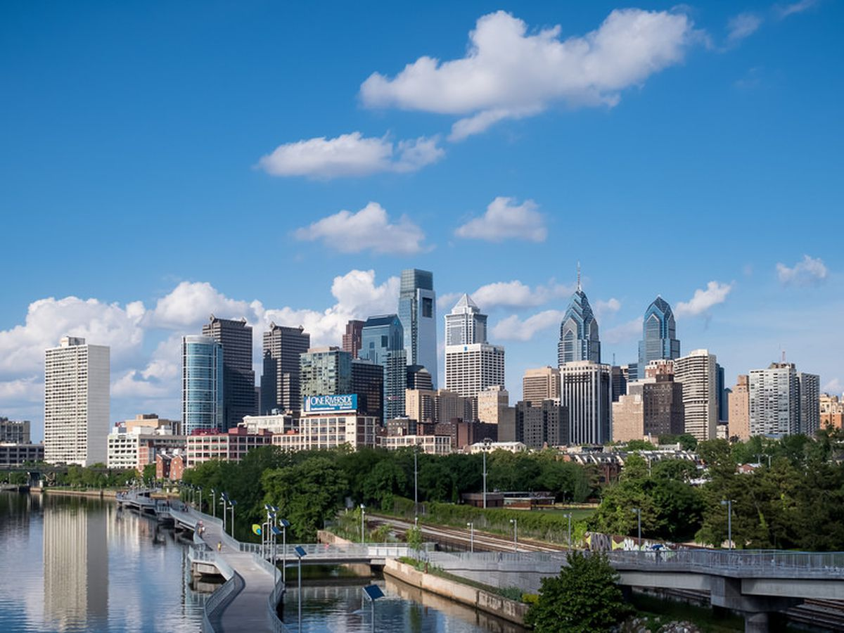 In the foreground is a river. In the distance is the Philadelphia skyline featuring many tall buildings.