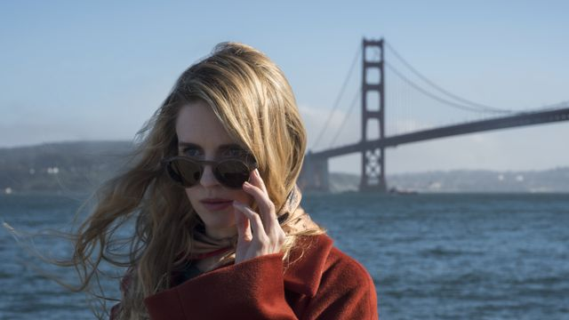 Brit Marling, a woman with blonde hair wearing a red coat, stands on the waterfront with the Golden Gate bridge in the background. She pulls her sunglasses partially down her face.