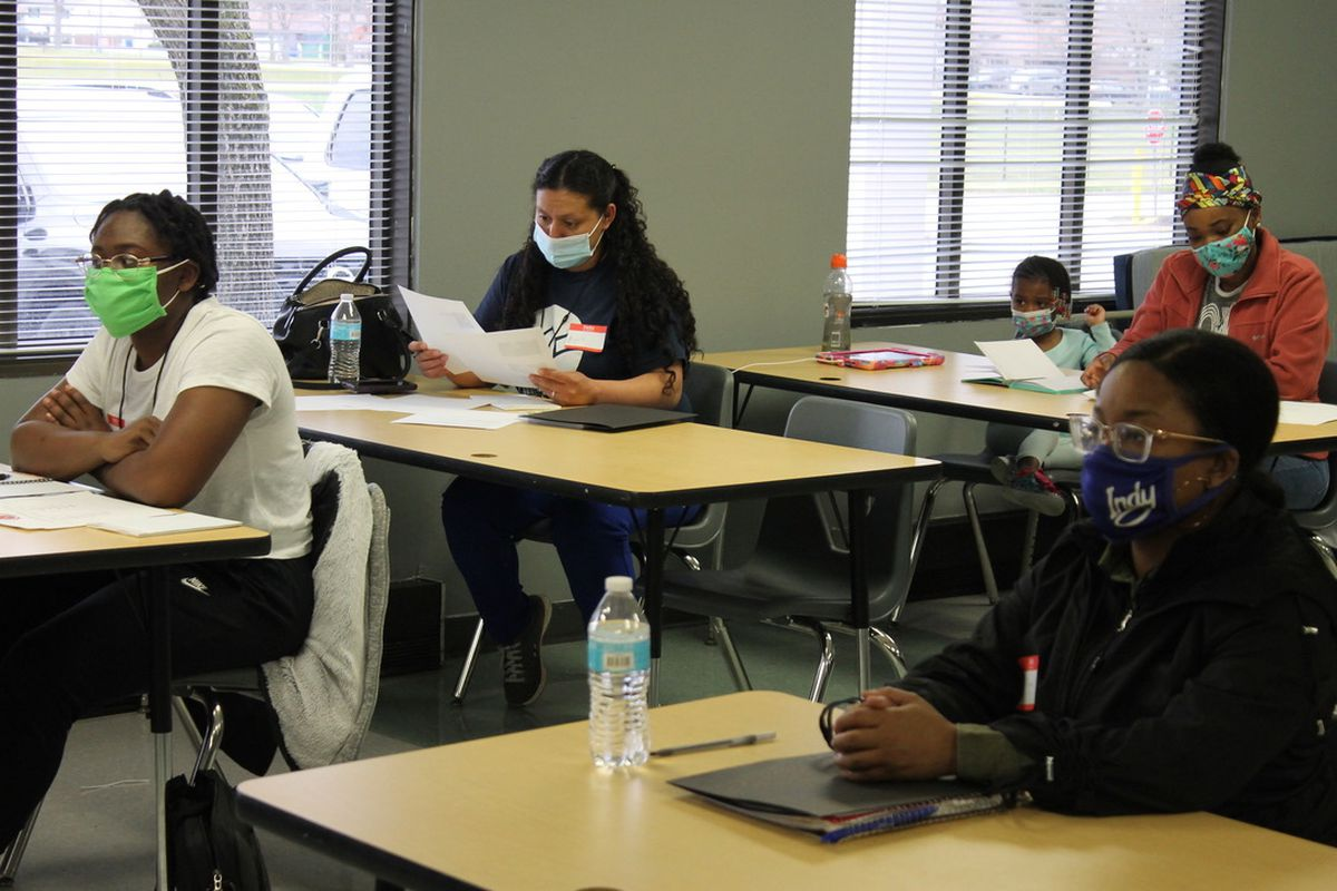 Four adult students wearing masks sit at spaced out desks in a classroom. One student has a small child next to her.