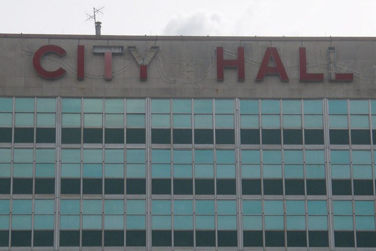 Large red letters spell CITY HALL above reflective blue windows on a tall cement building.