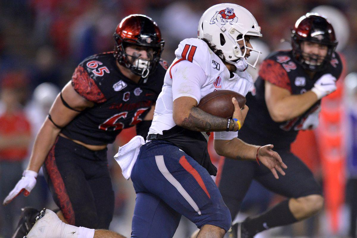 Fresno State Bulldogs quarterback Jorge Reyna (11) runs as San Diego State Aztecs defensive lineman Cameron Thomas (65) and linebacker Troy Cassidy (42) give chase at SDCCU Stadium.