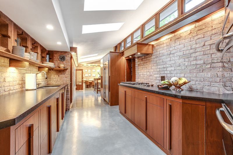 A long, narrow kitchen has slate kitchen counters, concrete floors, and wood cabinets.