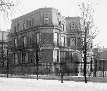 A large house with three floors. There is a fence surrounding the house.
