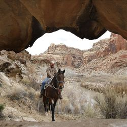 Kash Winn in framed by a small arch while riding horses down the Little Grand Canyon of the San Rafael Swell  Saturday, April 2, 2011, in the San Rafael Swell in Central Utah.