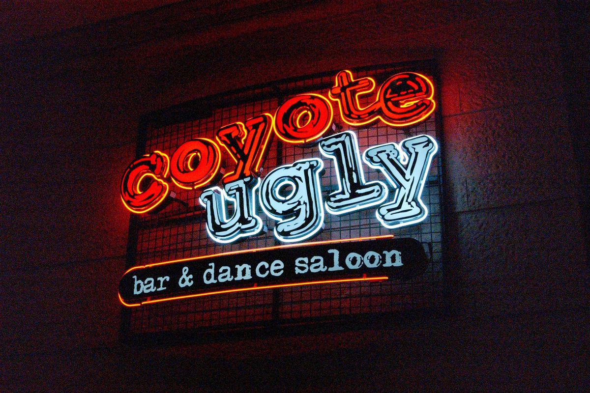 """A neon sign with the words """"Coyote Ugly Bar & Dance Saloon"""" in red and blue font"""