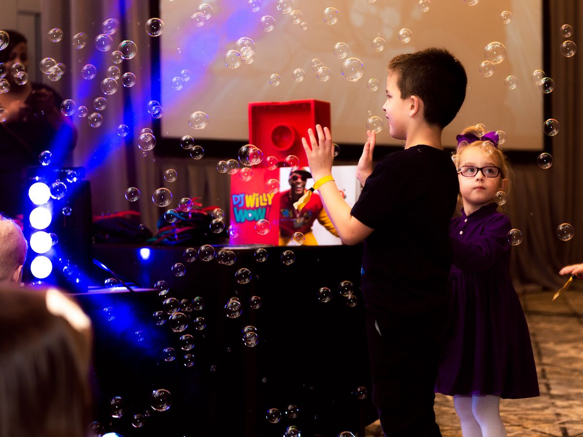 A young boy and girl playing with bubbles in the air.