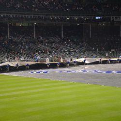 9:50 p.m. Grounds crew starts to remove the tarp -