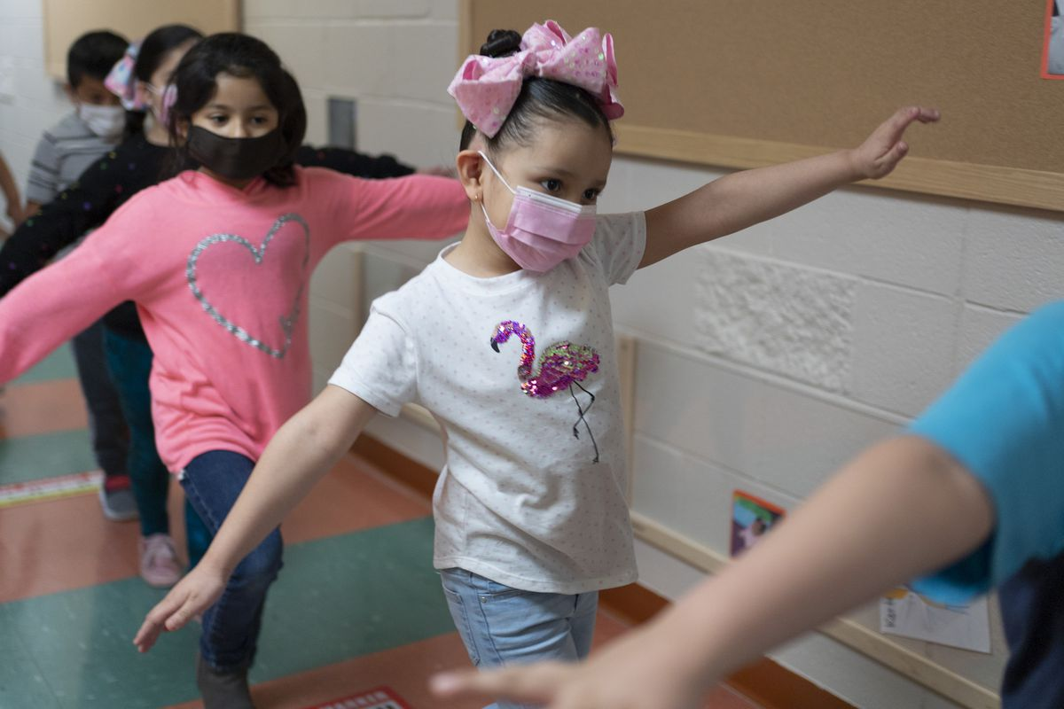 A child wearing a blue shirt is in front of a girl wearing a white flamingo shirt, a pink bow and a pink surgical mask, arms outstreched in a class hallway. The girl behind her is wearing a pink sweater with a silver heart on it.