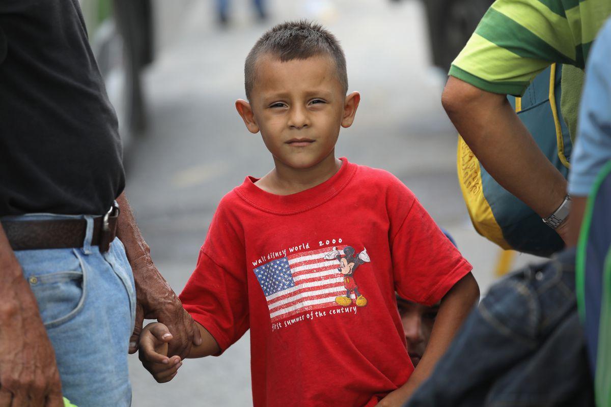 young boy waiting for migrant caravan