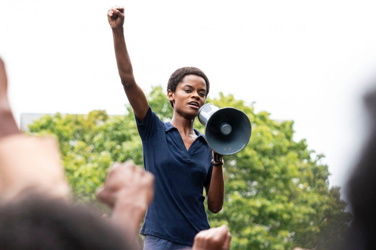 A woman stands with a raised fist and a megaphone.