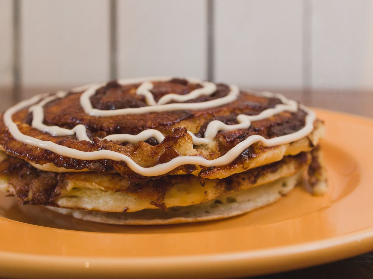 A stack of cinnamon roll flapjacks is drizzled with vanilla glaze and sitting on a plate