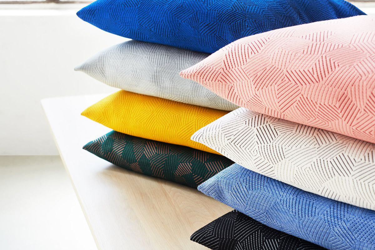 Pile of textured cushions in pink, grey, yellow, and blue.