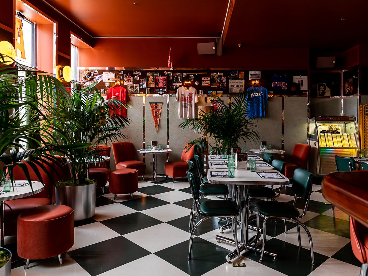 Memorabilia hangs on the walls surrounded by linoleum tables with green chairs, a Wurlitzer jukebox, and orange upholstered lounge seating.