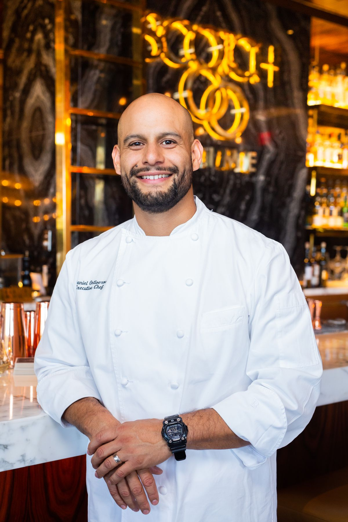 A chef poses in a white jacket