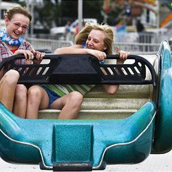 Friends Maddisen Gumeson, 13, and Madison Mangum, 13, both of Riverton, ride the Sizzler on Wednesday, the opening day of the Salt Lake County Fair in South Jordan. The fair runs through Saturday.