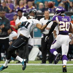 Jacksonville Jaguars wide receiver Laurent Robinson, left, makes a reception over Minnesota Vikings cornerback Chris Cook, right, during the first half of an NFL football game on Sunday, Sept. 9, 2012, in Minneapolis.