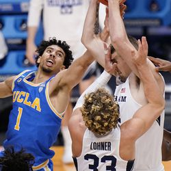 BYU center Richard Harward (42) grabs a rebound as teammate Caleb Lohner (33) and UCLA guard Jules Bernard (1) close in during the second half of a first-round game in the NCAA college basketball tournament at Hinkle Fieldhouse in Indianapolis, Saturday, March 20, 2021.