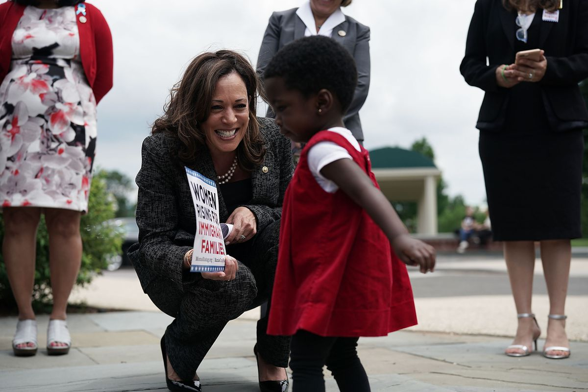 Senator Kamala Harris crouches down to smile at a toddler during a news conference.