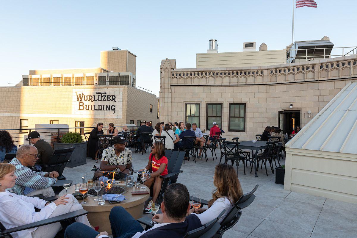 一群人坐在屋顶上的火坑周围,欣赏着高层建筑的景色