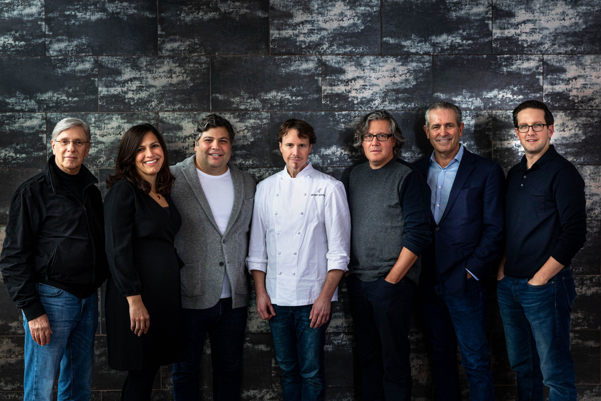 Seven people, the principals of Lettuce Entertain You Enterprises and the Alinea Group, pose standing against a blue wall.