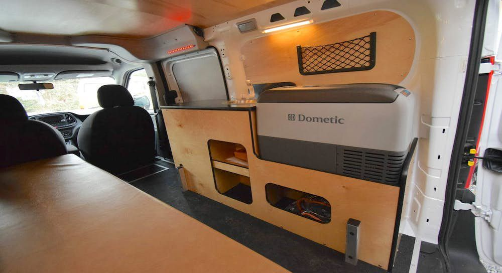 The interior of a camper van. There is a shelf and other storage areas.
