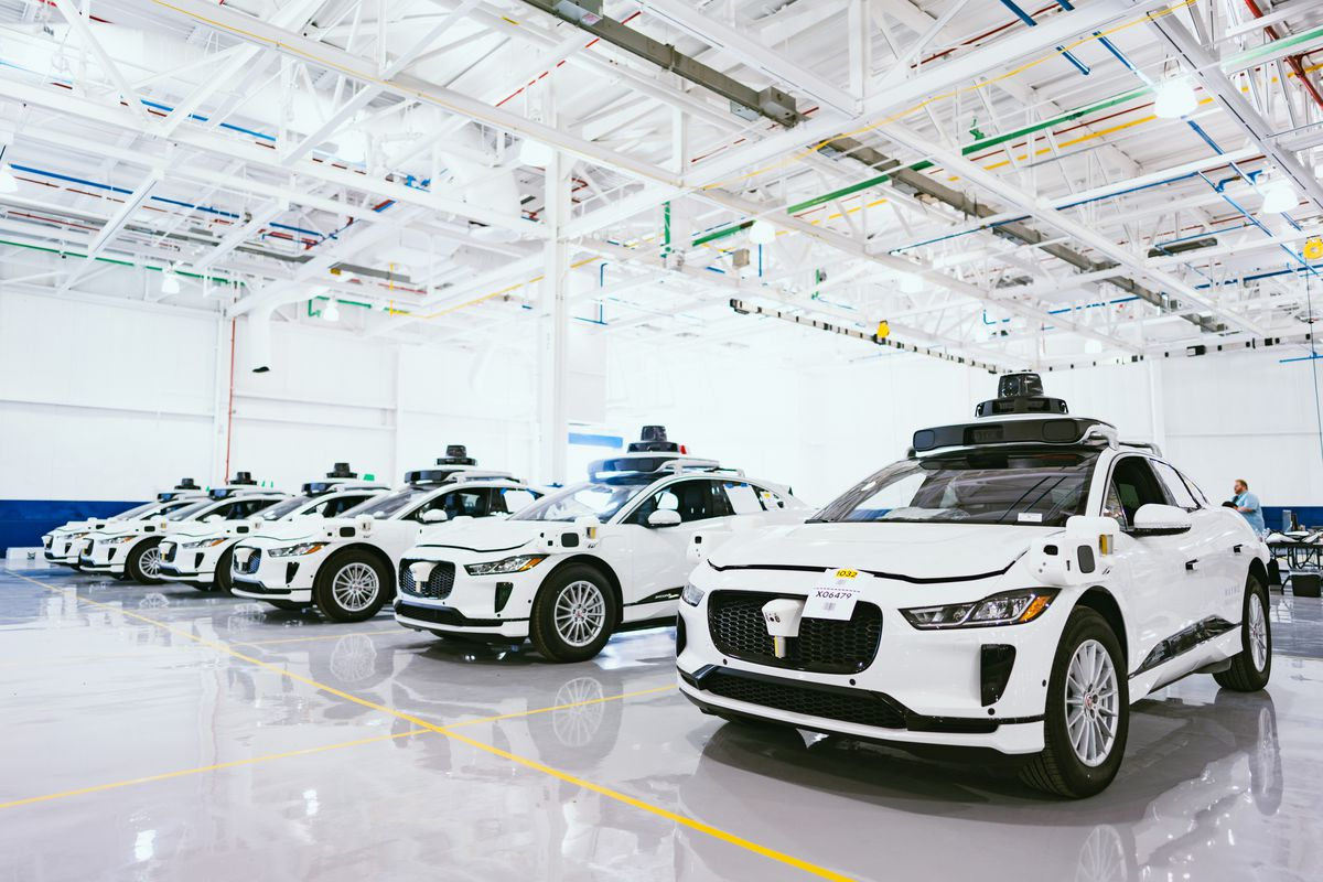 A row of six white sedans idle in a large warehouse with with steel beams in the ceiling. There are black cameras mounted on top of the cars.