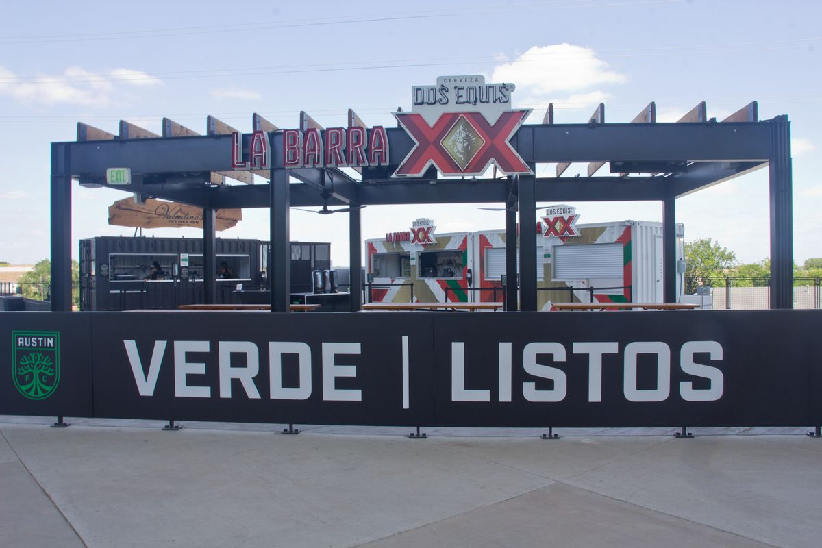 """An open black structure with a sign that reads """"La Barra Dos Equis XX"""" with a black fence sign that reads """"Verde 