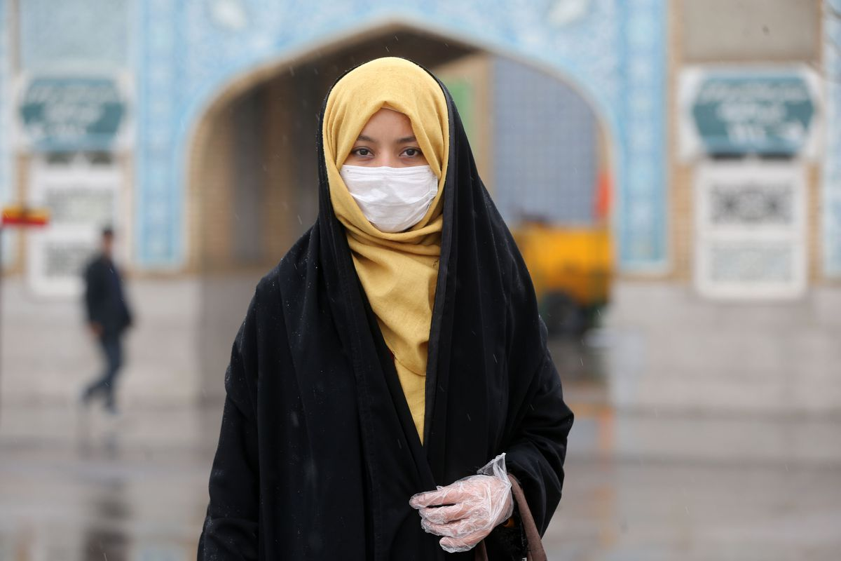 A woman in a headscarf wearing a respiratory mask.