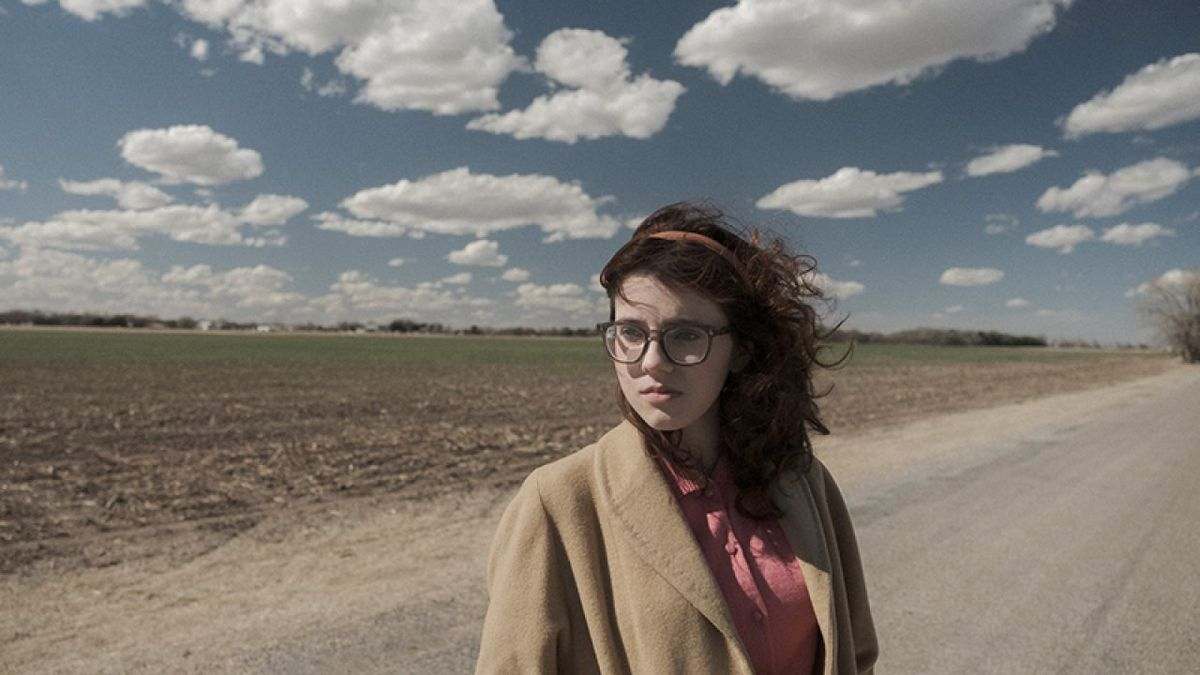 Kara Hayward as a young girl in the 1950s standing in a dusty road in To the Stars