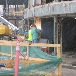 11:08 a.m. Workers using a torch, cutting something away, where the ticket windows are located -