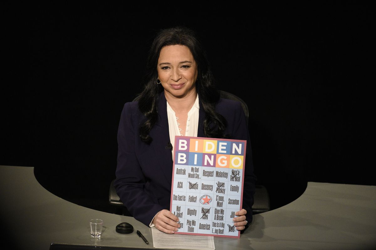 "Maya Rudolph, wearing the blue suit and white shirt Kristen Welker did during the final presidential debate, sits at a desk, holding up a ""Biden Bingo"" card. A few boxes are scratched out, and there is a shot glass next to her."