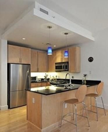 A shot of an open kitchen with two chairs in front of the counter that separates the kitchen from the living room.