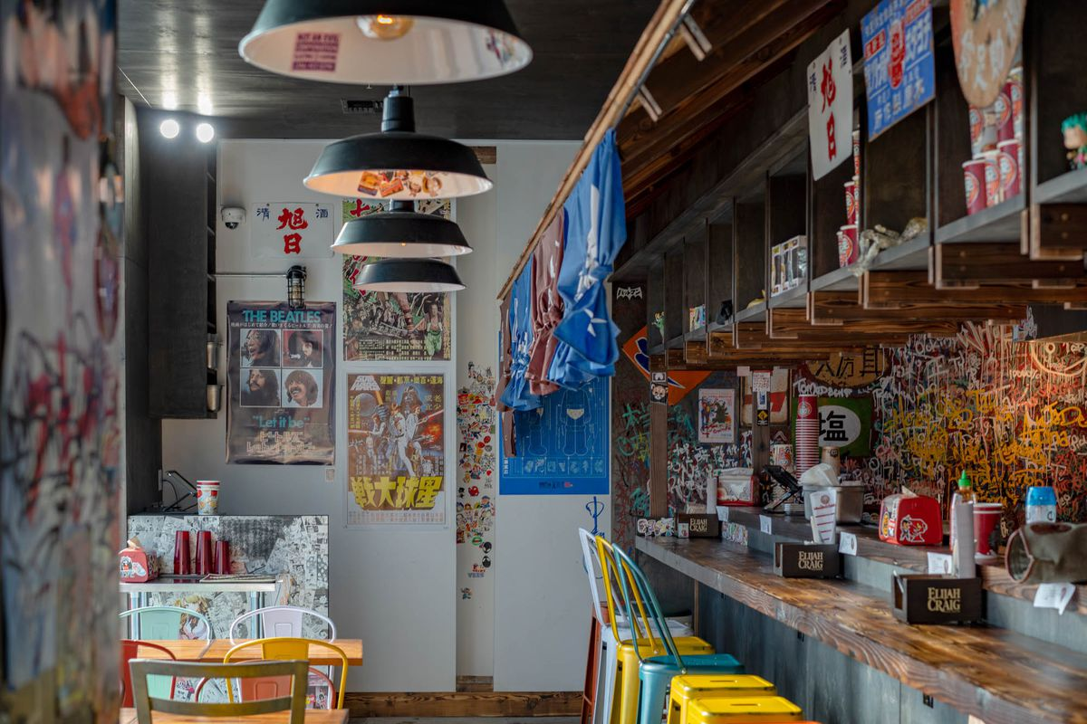 The counter space at Taku with colorful stools and hanging lights and banners overhead.