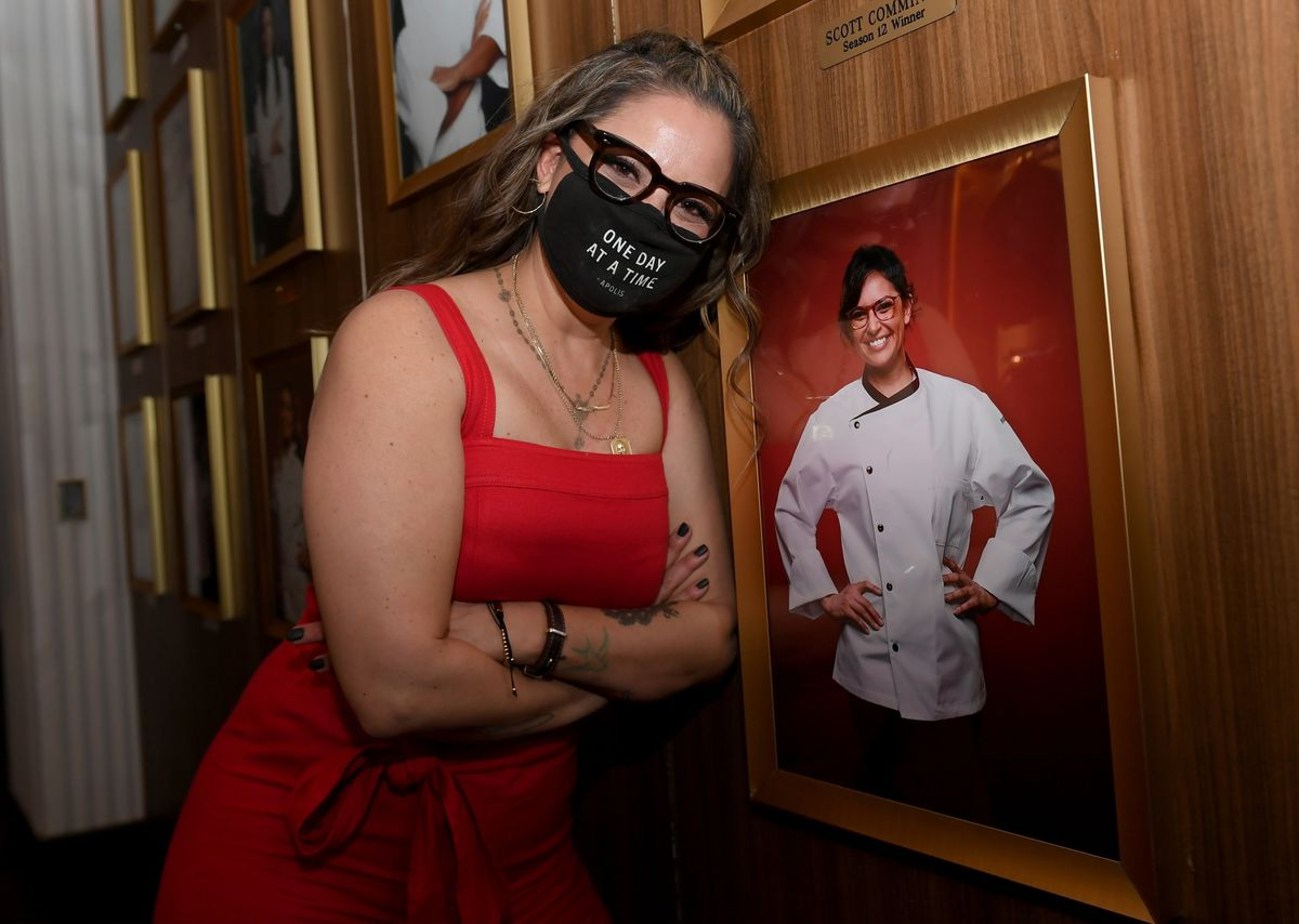 A woman wearing a mask shows of a photo of herself
