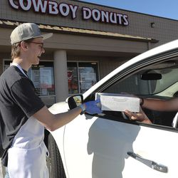 Blake Turner delivers a box of donuts to customer Jon Wardenburg outside Cowboy Donuts in Spanish Fork on Tuesday, April 14, 2020. Podium has developed and released, free of charge, an interface that allows food businesses to operate takeout services entirely on a text chain from ordering to payment.