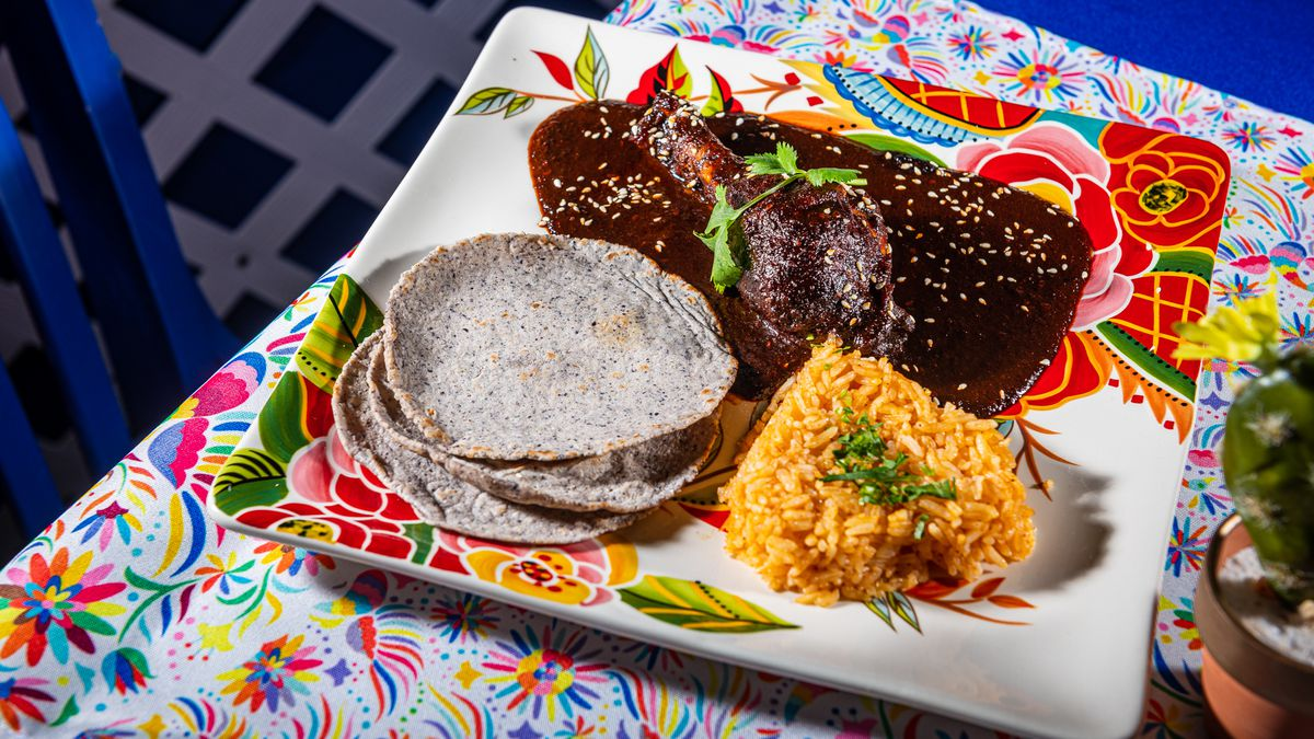 Pollo con Mole (chicken topped with red mole, served with rice and fresh tortillas) from Corazon.