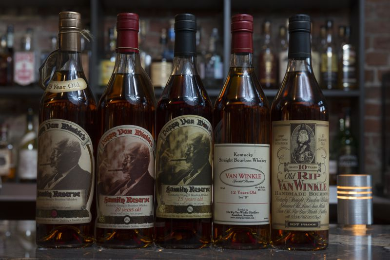 Five different bottles of Pappy Van Winkle, Van Winkle, and Old Rip Van Winkle bourbon sitting on  a bar top with other bottles in the background.