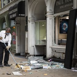 A man sweeps up outside Paul Young Fine Jewelers at 34 W. Randolph St. after looting broke out in the Loop and surrounding neighborhoods overnight, Monday morning, Aug. 10, 2020.