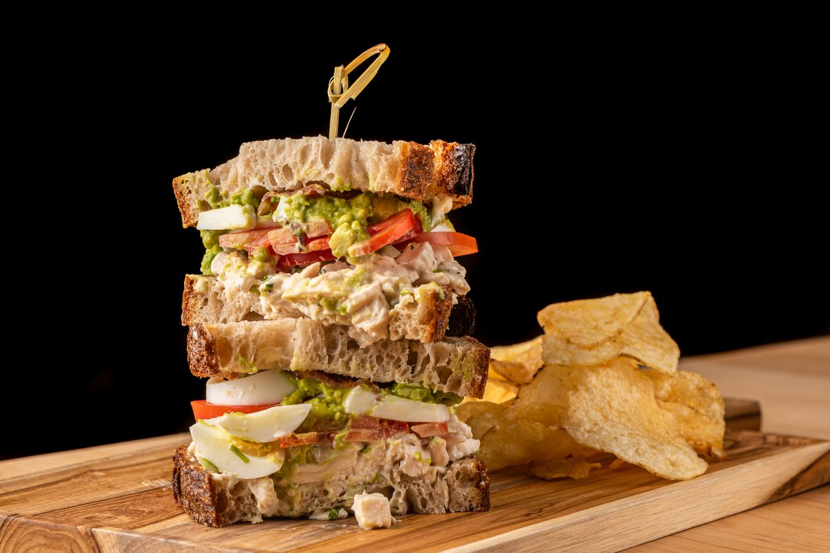 A side angle view of a cut sandwich with chicken cubes spilling out.