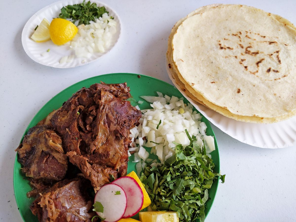 On a green plate, a giant hunk of meat with onions and cilantro, and a side plate of tortillas.