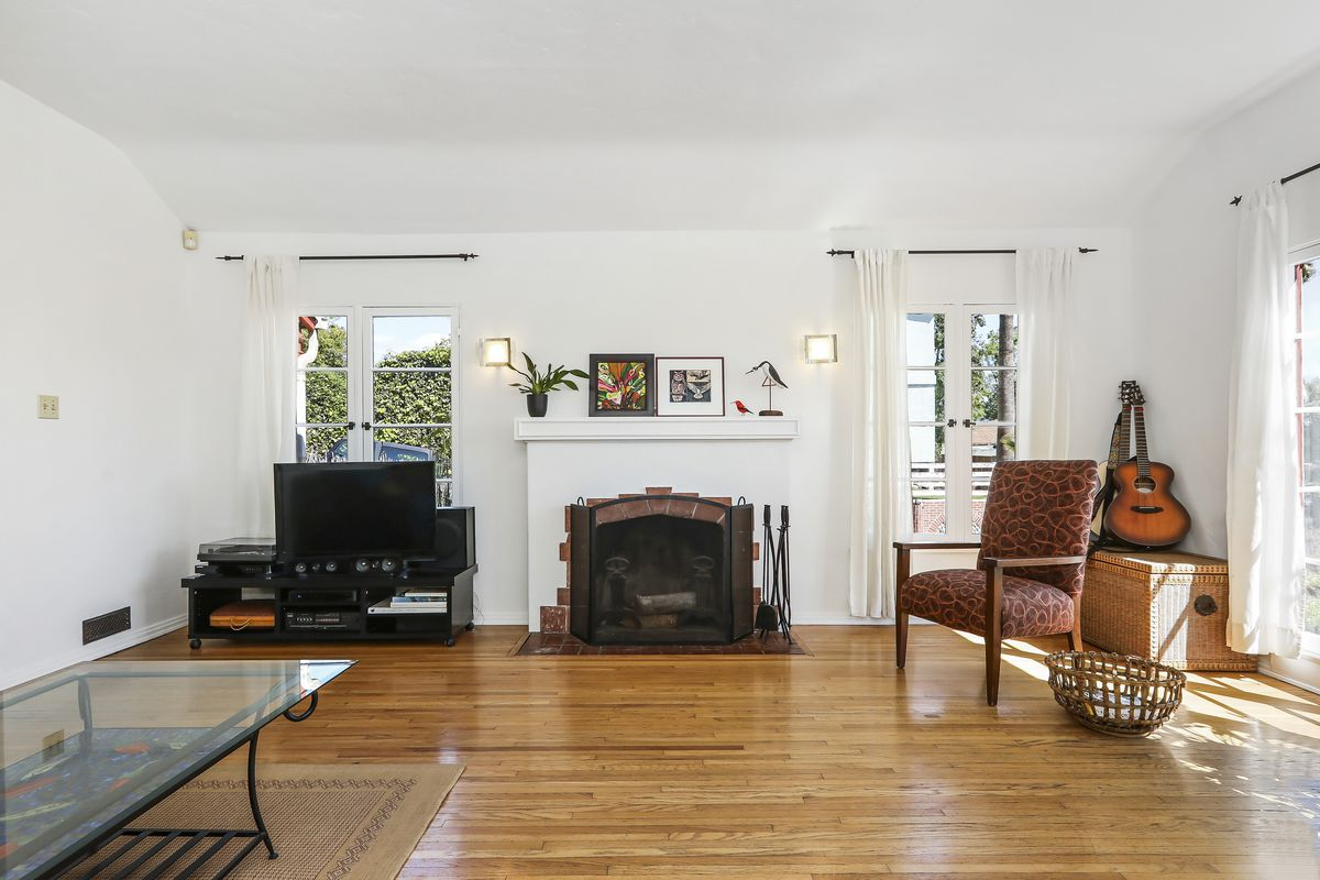 A room with wood floors and white walls. At the far wall is a fireplace with windows on either side.
