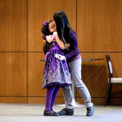 Carol Wang, 9, is congratulated by her mother, Sui Zhang, after performing the national anthem during tryouts at EnergySolutions Arena in Salt Lake City on Friday, Oct. 4, 2013. The winners will perform the anthem prior to each Utah Jazz home game during the 2013-2014 season.