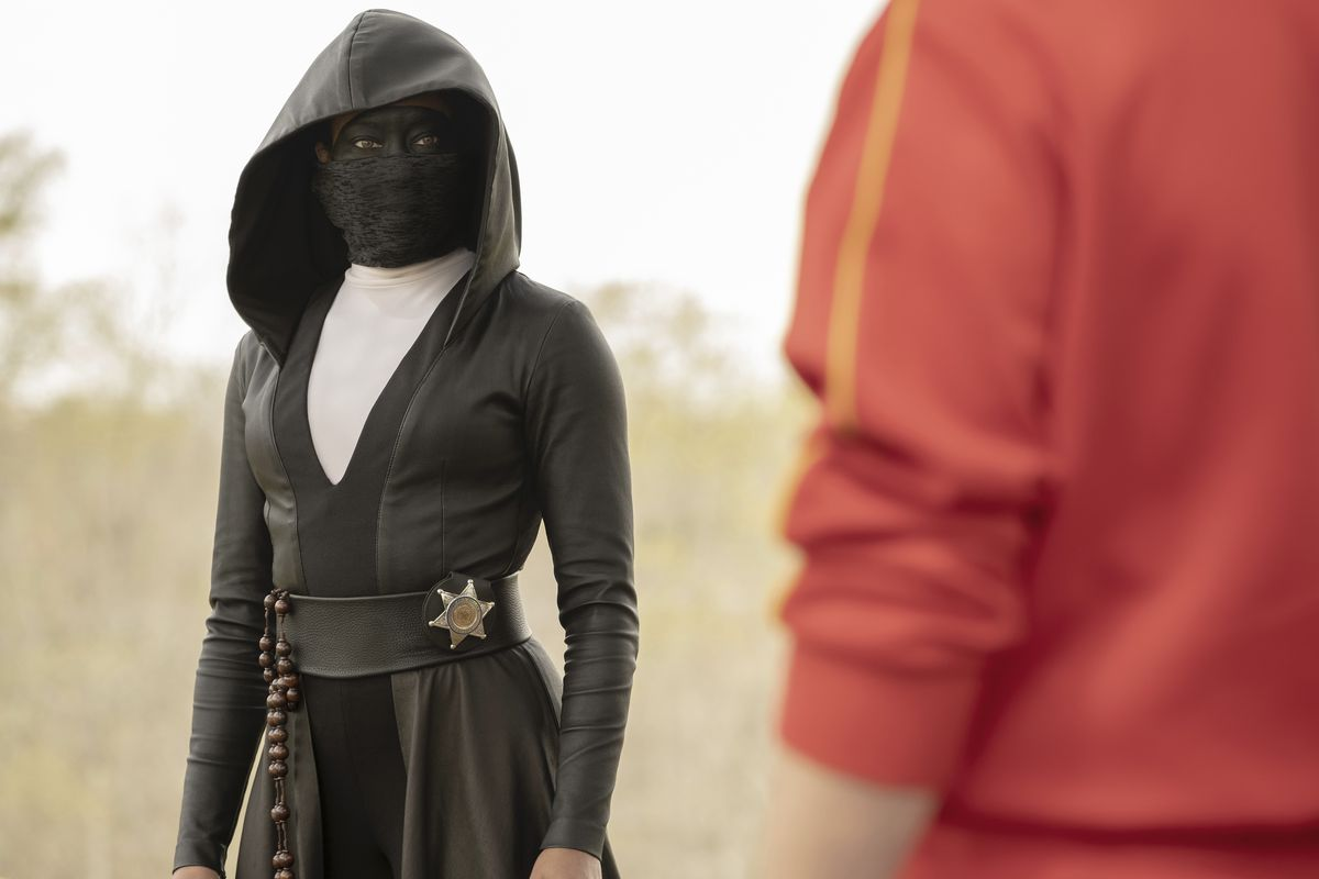 Masked police officer Sister Night (Regina King) stares down an unknown character.
