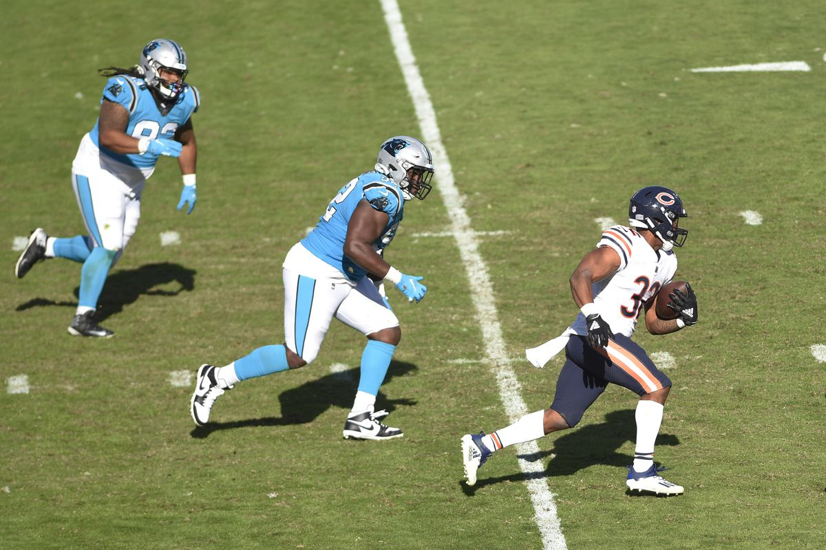 Chicago Bears running back David Montgomery (32) wirh the ball as Carolina Panthers defensive tackles Zach Kerr (92) and Bravvion Roy (93) defend in the fourth quarter at Bank of America Stadium.